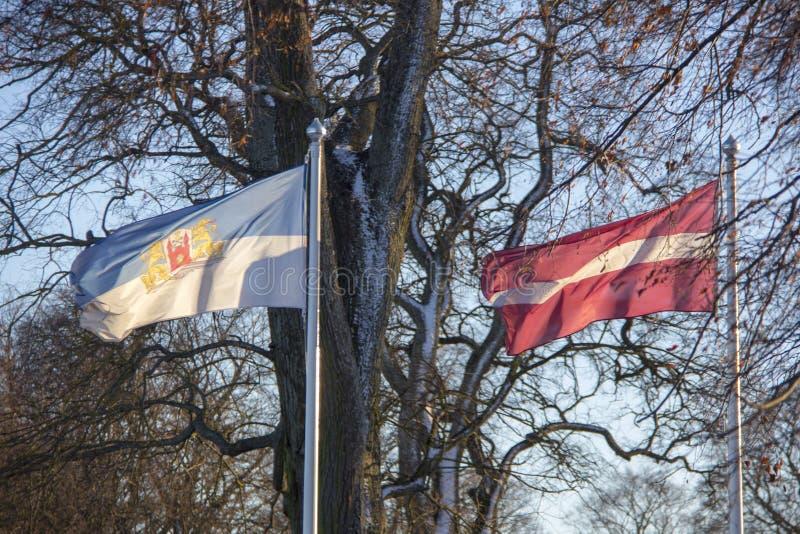 Bandera de Riga y de Letonia en invierno fotografía de archivo
