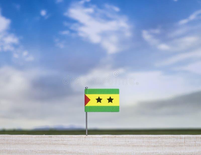 Bandera de São Tomé y de PrÃncipe con el prado extenso y el cielo azul detrás de él imagenes de archivo