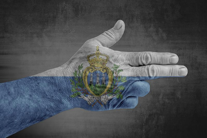Bandera de San Marino pintada en la mano masculina como un arma foto de archivo libre de regalías