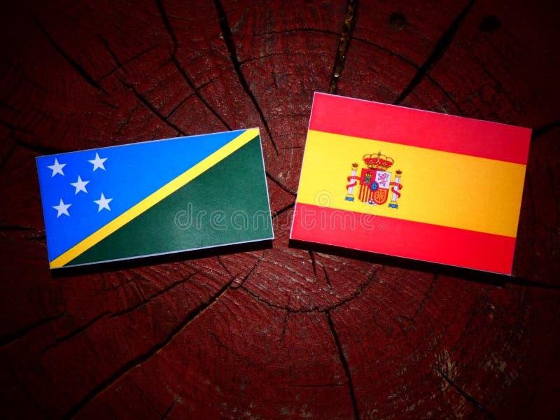 Bandera de Solomon Islands con la bandera española en un tocón de árbol fotografía de archivo libre de regalías