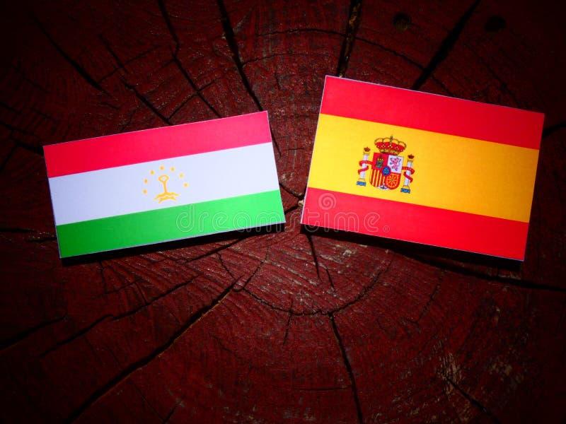 Bandera de Tayikistán con la bandera española en un tocón de árbol fotos de archivo libres de regalías