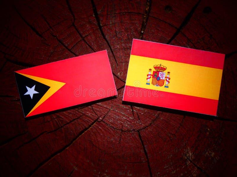 Bandera de Timor del Este con la bandera española en un tocón de árbol imágenes de archivo libres de regalías