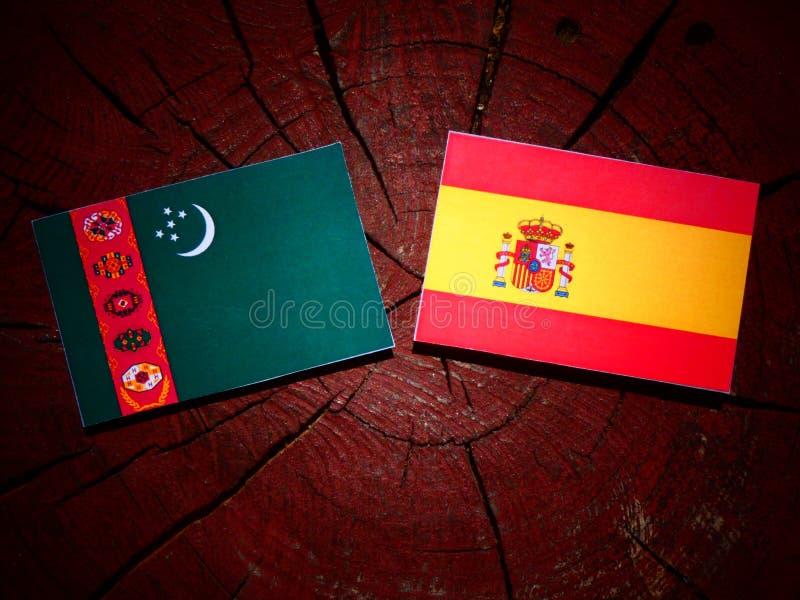 Bandera de Turkmenistán con la bandera española en un tocón de árbol fotos de archivo