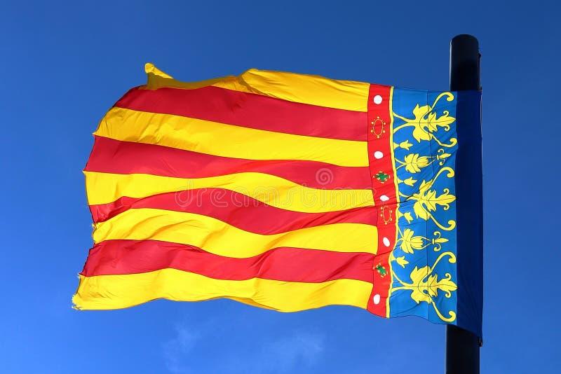 Bandera de Valencia, España, agitando en el viento delante de un cielo azul, aislado y iluminado por el sol imagen de archivo libre de regalías