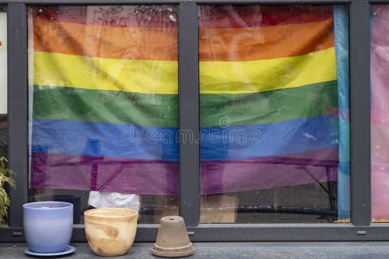 Bandera del arco iris en ventana imágenes de archivo libres de regalías