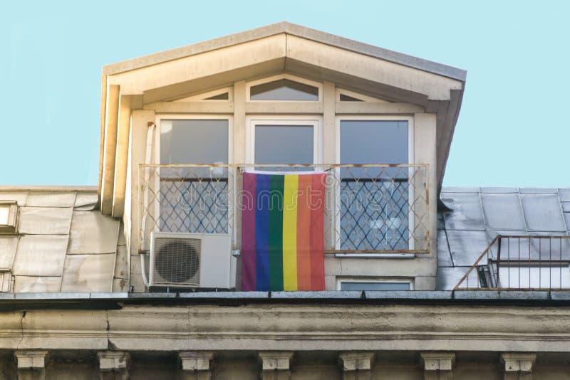 Bandera del arco iris LGBT - bandera de la comunidad lesbiana, del gay y del transexual en ventana imágenes de archivo libres de regalías