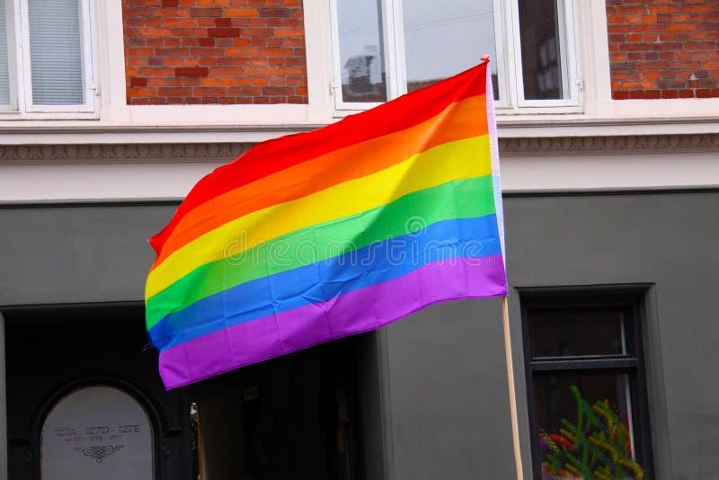 Bandera del arco iris que agita en ciudad en el desfile de orgullo - símbolo de LGBT - para el gay, relación de la lesbiana, del  fotos de archivo libres de regalías