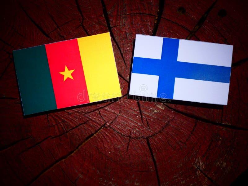 Bandera del Camerún con la bandera finlandesa en un tocón de árbol aislado fotos de archivo