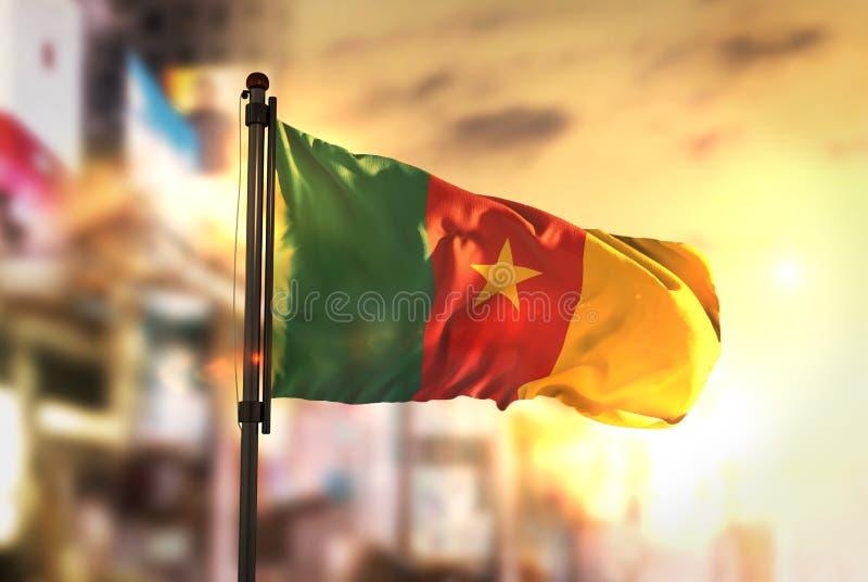 Bandera del Camerún contra fondo borroso ciudad en la salida del sol Backlig fotografía de archivo libre de regalías