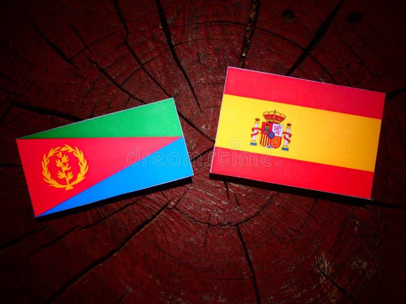 Bandera del Eritrean con la bandera española en un tocón de árbol imagenes de archivo
