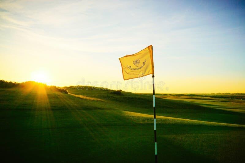 Bandera del golf en la subida del sol imagenes de archivo