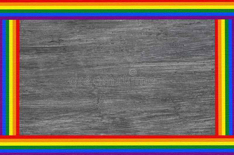 Bandera del marco de texto de la bandera del arco iris de LGBT aislada en fondo de madera gris imagen de archivo