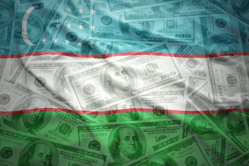 bandera del uzbek que agita en un fondo americano del dinero del dólar foto de archivo