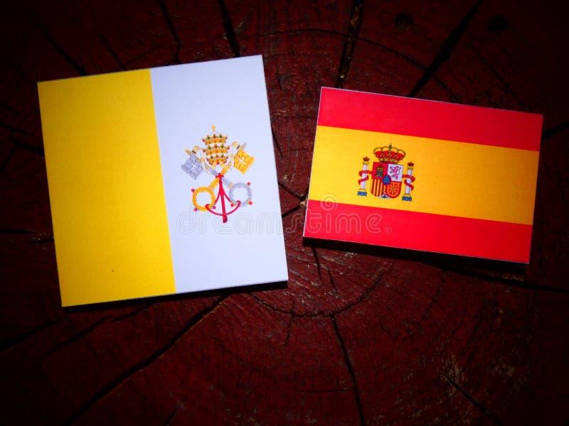 Bandera del Vaticano con la bandera española en un tocón de árbol foto de archivo