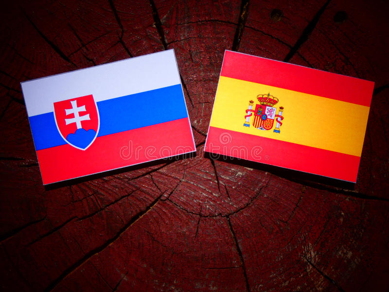 Bandera eslovaca con la bandera española en un tocón de árbol fotografía de archivo