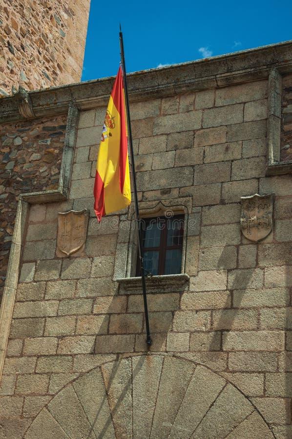 Bandera española alzada sobre una puerta en una fachada constructiva gótica en Caceres fotos de archivo