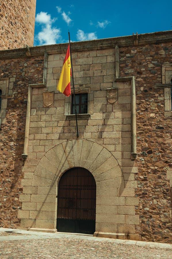 Bandera española alzada sobre una puerta en una fachada constructiva gótica en Caceres fotos de archivo libres de regalías