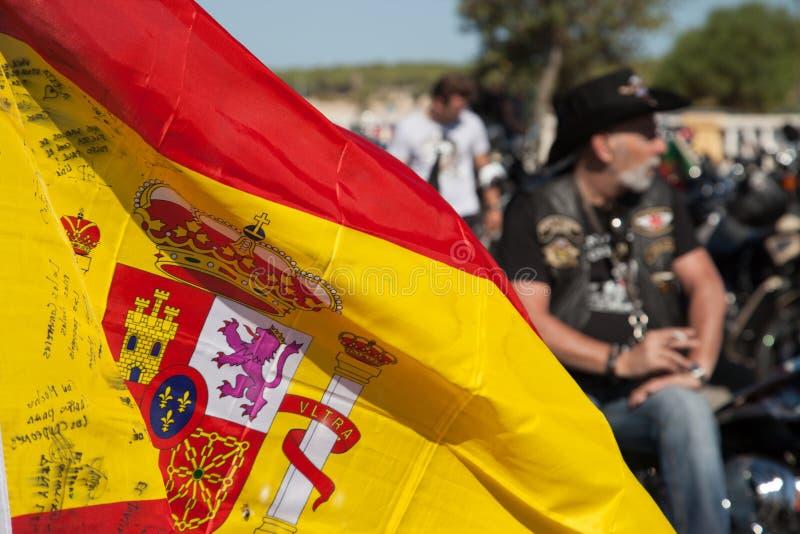 Bandera española con el motorista en la reunión del cerdo del fondo fotos de archivo