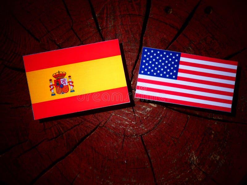 Bandera española con la bandera de los E.E.U.U. en un tocón de árbol imagenes de archivo