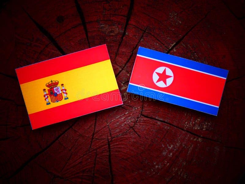 Bandera española con la bandera norcoreana en un tocón de árbol fotos de archivo