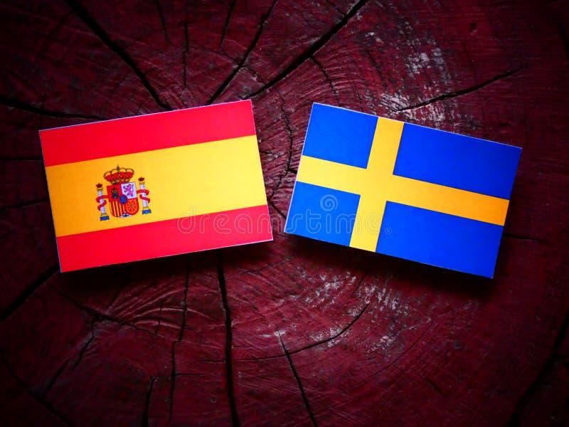 Bandera española con la bandera sueca en un tocón de árbol fotos de archivo