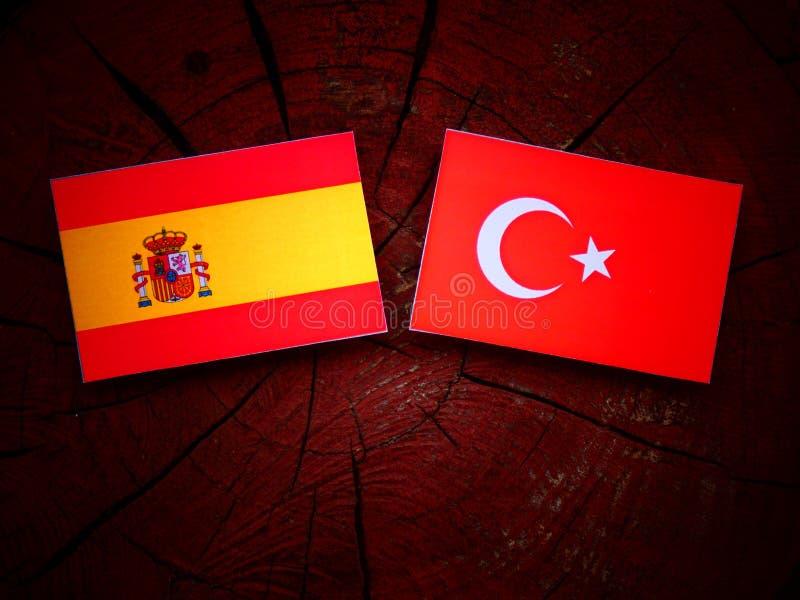 Bandera española con la bandera turca en un tocón de árbol imagenes de archivo