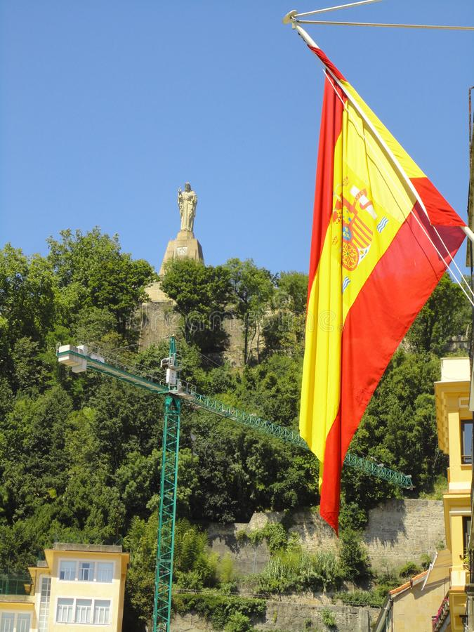 Bandera española con la estatua de Jesus Christ en el fondo imagen de archivo libre de regalías