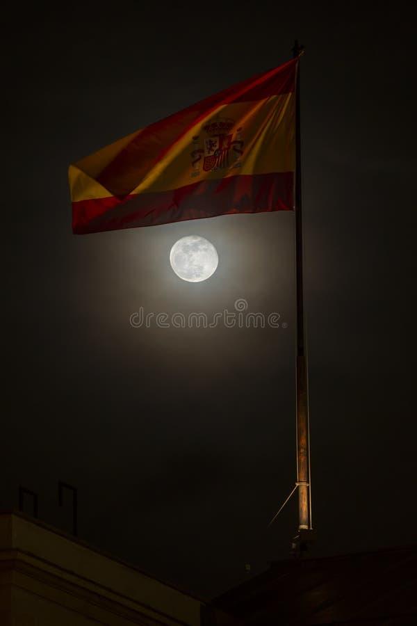 Bandera española con la luna en la noche imagenes de archivo