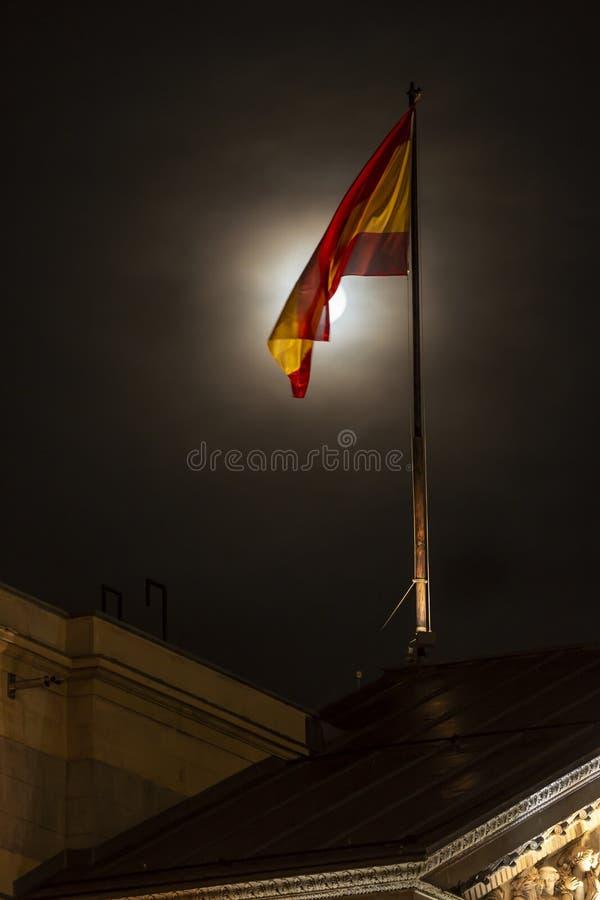 Bandera española con la luna en la noche fotos de archivo