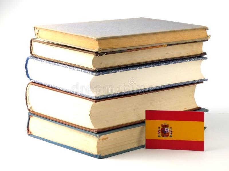 Bandera española con la pila de libros en el fondo blanco imagen de archivo libre de regalías