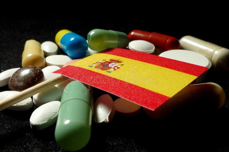 Bandera española con la porción de píldoras médicas aisladas en backgro negro foto de archivo