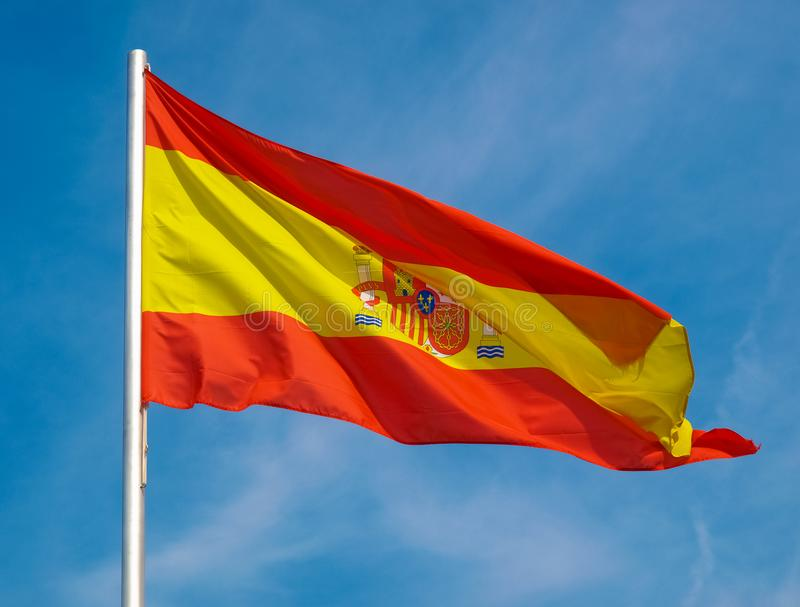 Bandera española de España sobre el cielo azul foto de archivo