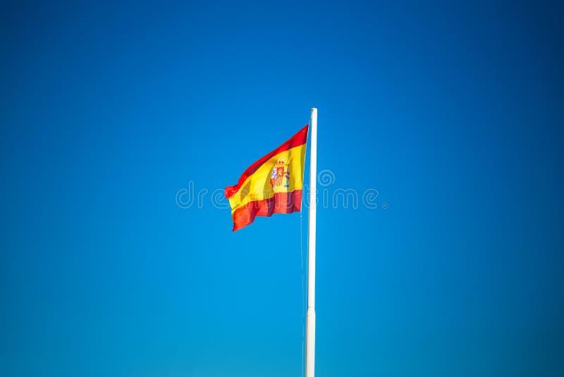 Bandera española en el cielo azul sin las nubes imagen de archivo