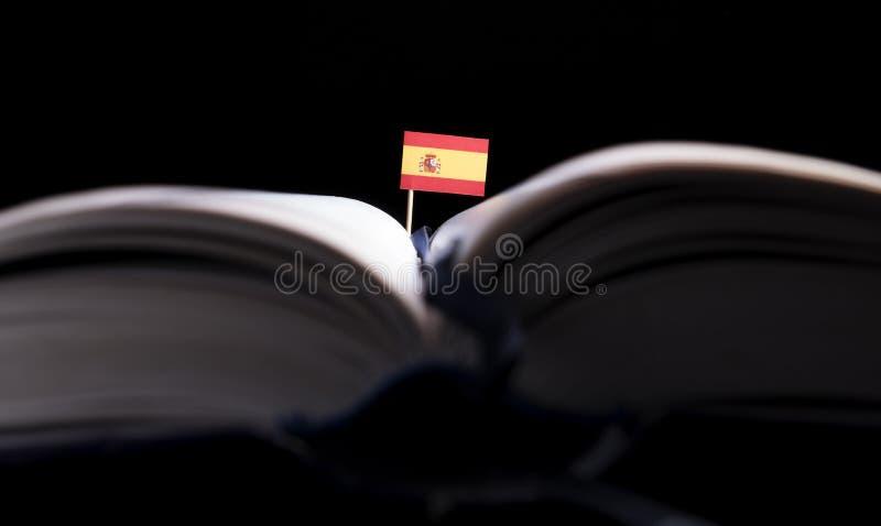 Bandera española en el medio del libro Conocimiento y educación fotos de archivo