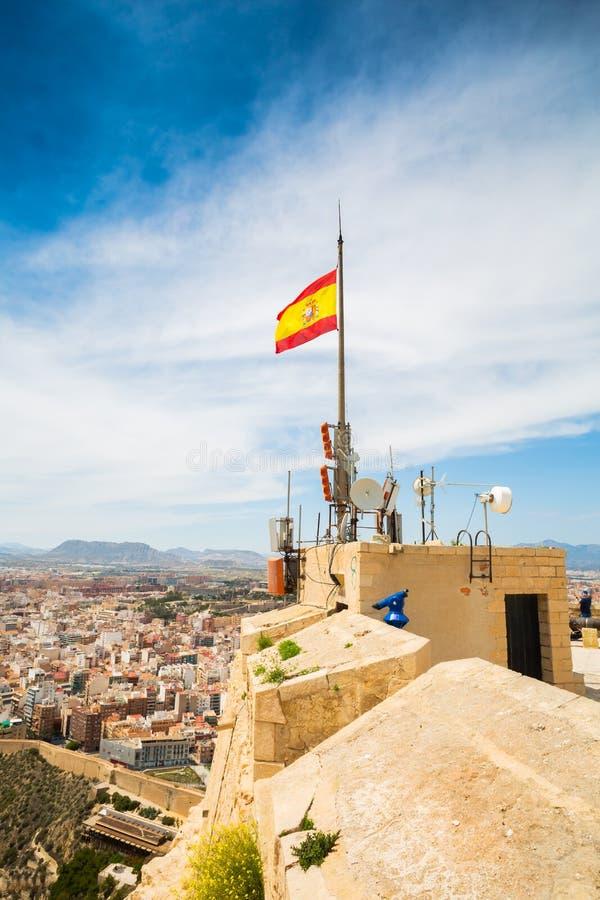 Bandera española en el top de Santa Barbara Castle en la montaña de Benacantil foto de archivo libre de regalías