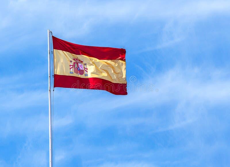 Bandera española en fondo del cielo azul imagen de archivo libre de regalías