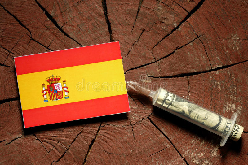 Bandera española en un tocón con la jeringuilla que inyecta el dinero foto de archivo libre de regalías