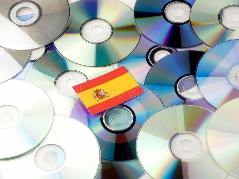 Bandera española encima de la pila del CD y del DVD aislada en blanco imagenes de archivo