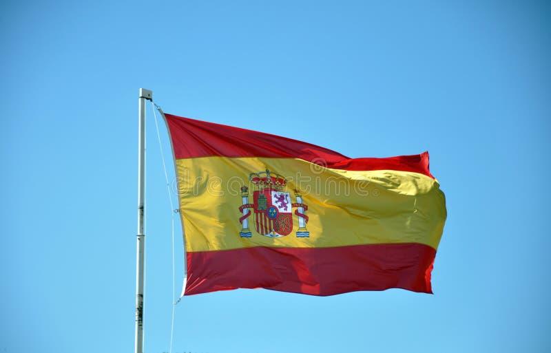 Bandera española ondeando el cielo azul imagen de archivo