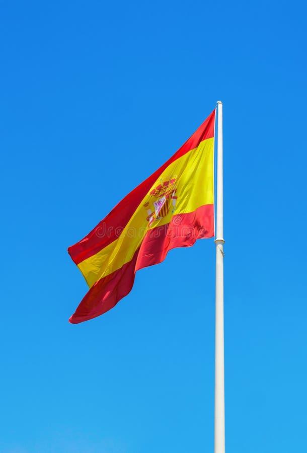 Bandera española que agita contra el cielo azul claro fotografía de archivo