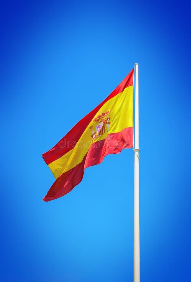 Bandera española que agita contra el cielo azul claro foto de archivo