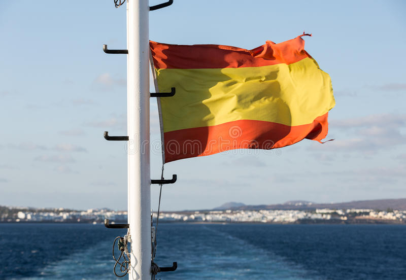 Bandera española que agita en un barco, en un día soleado imagenes de archivo