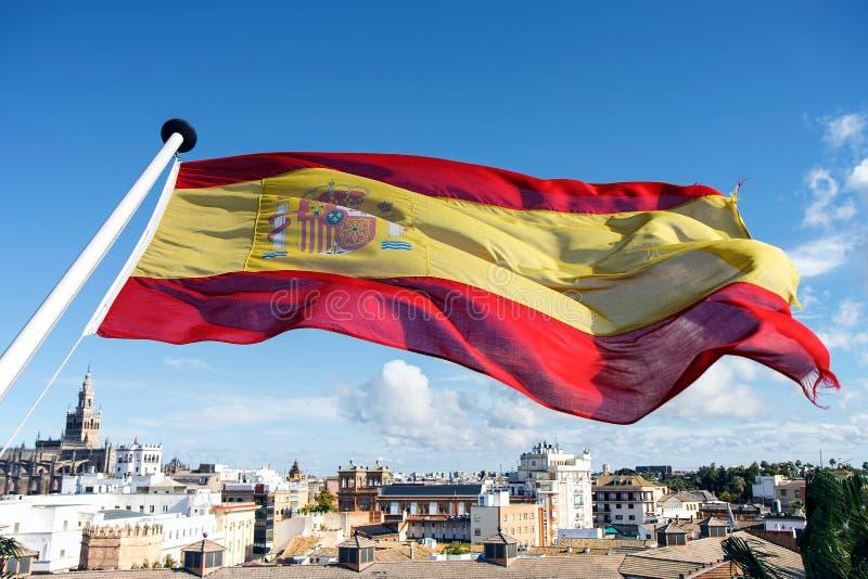 Bandera española que vuela sobre la ciudad de Sevilla imagen de archivo libre de regalías