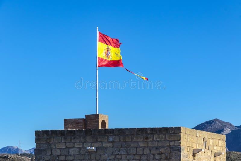 Bandera española rasgada que agita en el viento fotos de archivo
