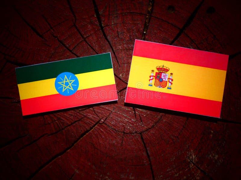 Bandera etíope con la bandera española en un tocón de árbol imagen de archivo