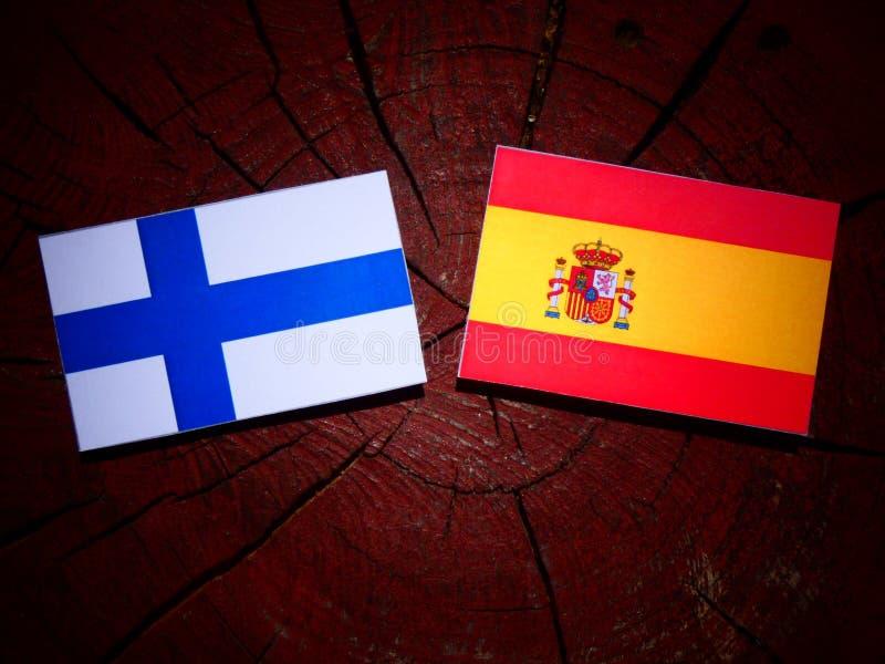 Bandera finlandesa con la bandera española en un tocón de árbol fotos de archivo libres de regalías