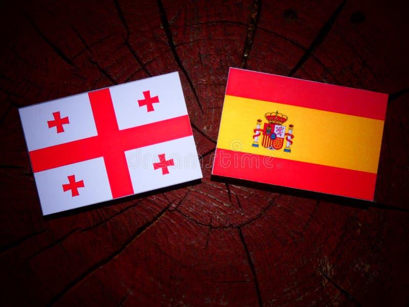 Bandera georgiana con la bandera española en un tocón de árbol fotos de archivo