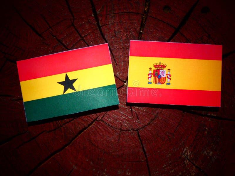 Bandera ghanesa con la bandera española en un tocón de árbol imagenes de archivo