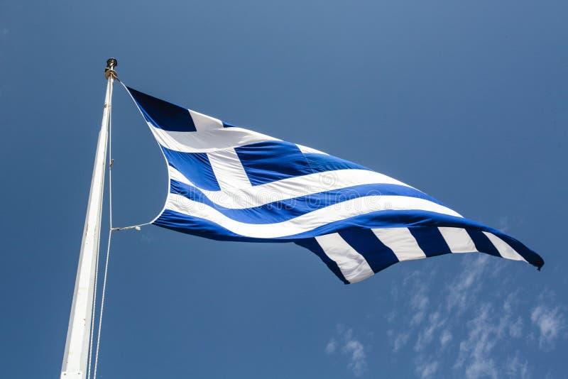 Bandera griega en el viento contra un cielo azul del verano fotografía de archivo