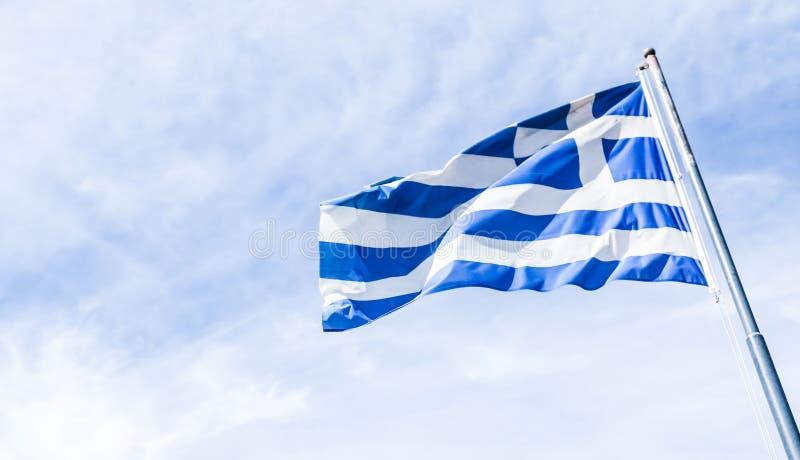 Bandera griega y cielo nublado en el d?a de verano, pol?tica de Europa fotografía de archivo